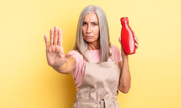 Mulher bonita de meia-idade olhando sério, mostrando a palma da mão aberta, fazendo gesto de parada. conceito de ketchup