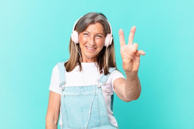 Mulher bonita de meia-idade ouvindo música com fones de ouvido