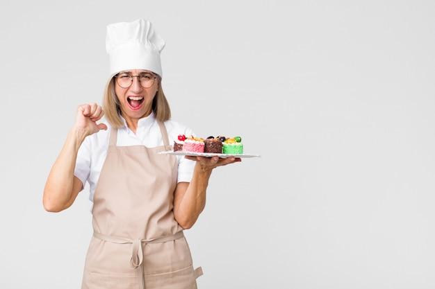 Mulher bonita de meia idade padeiro com bolos