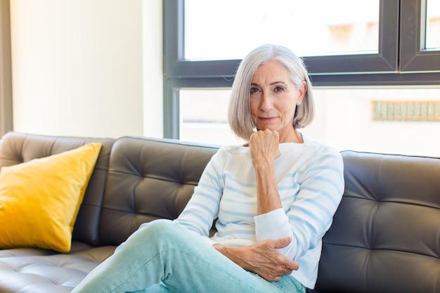 Mulher bonita de meia-idade parecendo feliz e sorrindo com a mão no queixo, pensando ou fazendo uma pergunta, comparando opções