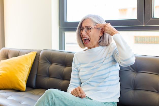 Mulher bonita de meia-idade parecendo infeliz e estressada, gesto suicida fazendo sinal de arma com a mão, apontando para a cabeça