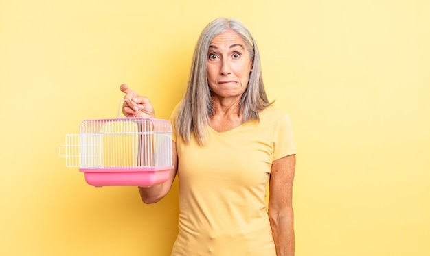 Mulher bonita de meia-idade parecendo perplexa e confusa. conceito de gaiola ou prisão para animais de estimação