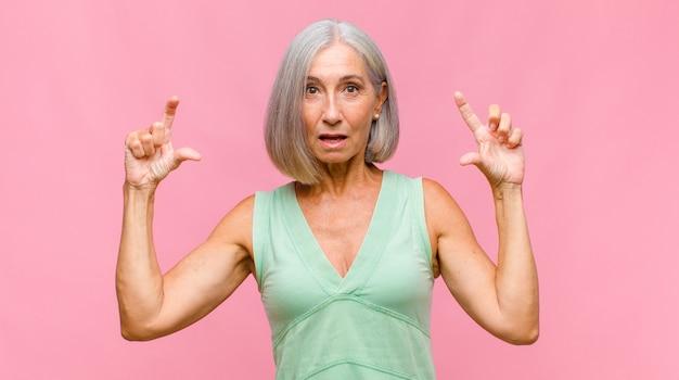 Mulher bonita de meia-idade parecendo perplexa e confusa, insegura e apontando em direções opostas com dúvidas