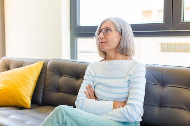 Mulher bonita de meia-idade parecendo perplexa e confusa, pensando ou tentando resolver um problema ou pensamento