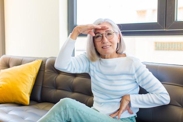 Mulher bonita de meia-idade parecendo perplexa e surpresa, com a mão na testa olhando para longe, observando ou procurando
