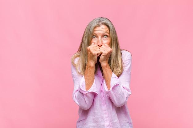 Mulher bonita de meia-idade parecendo preocupada, ansiosa, estressada e com medo, roendo as unhas e olhando para o espaço da cópia lateral