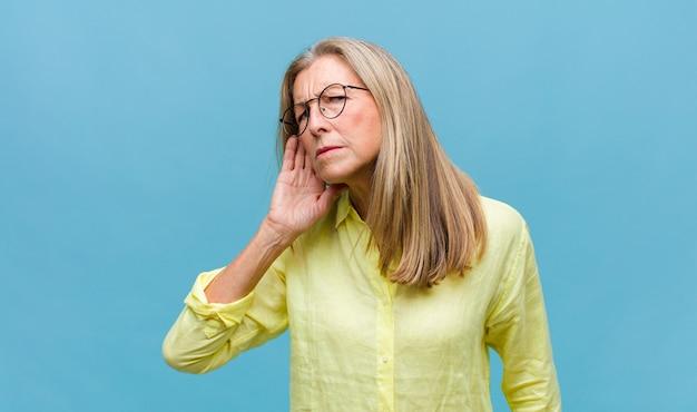 Mulher bonita de meia-idade parecendo séria e curiosa, ouvindo, tentando ouvir uma conversa secreta ou fofoca