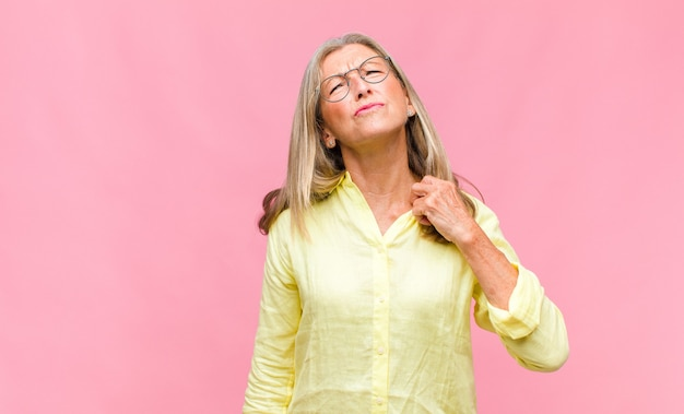 Mulher bonita de meia-idade parecendo séria e descontente com os dois dedos cruzados na frente em rejeição, pedindo silêncio