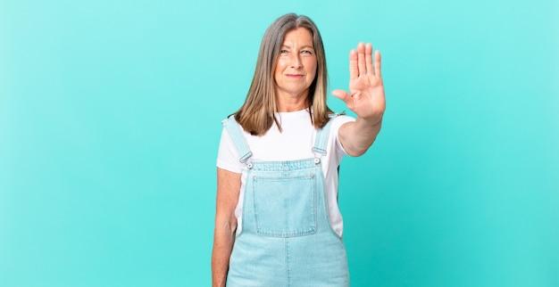 Mulher bonita de meia-idade parecendo séria, mostrando a palma da mão aberta fazendo gesto de pare