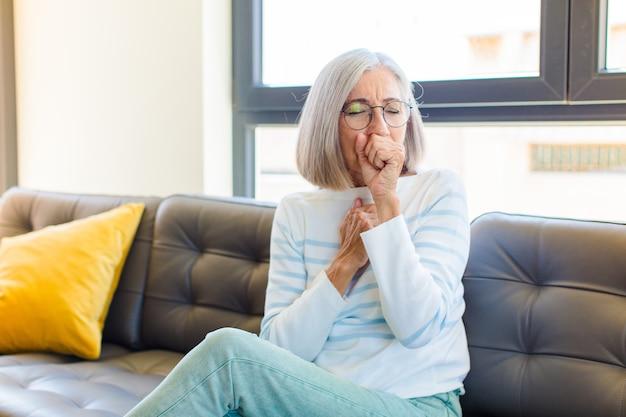 Mulher bonita de meia-idade passando mal com dor de garganta e sintomas de gripe, tosse com a boca coberta