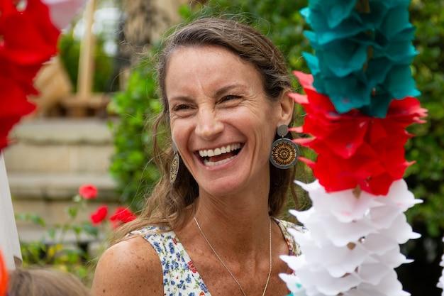 Mulher bonita de meia idade rindo enquanto segura o arco de celebração basco tradicional. retrato de uma linda senhora desfrutando da cerimônia de casamento