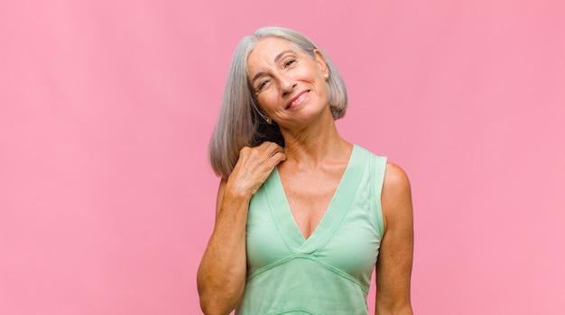 Mulher bonita de meia-idade se sentindo apaixonada, sorrindo, acariciando e se abraçando, permanecendo solteira, sendo egoísta e egocêntrica