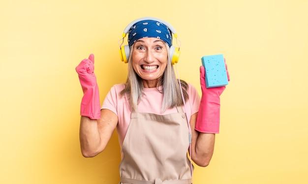Mulher bonita de meia-idade se sentindo chocada, rindo e comemorando o sucesso. limpador de esfregão