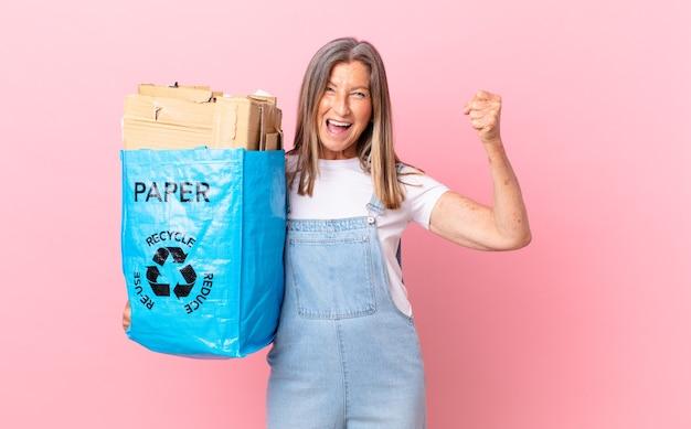 Mulher bonita de meia-idade se sentindo chocada, rindo e comemorando o sucesso, reciclando o conceito de papelão