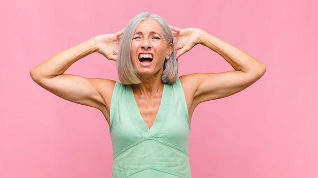 Mulher bonita de meia-idade se sentindo estressada, preocupada, ansiosa ou com medo, com as mãos na cabeça e entrando em pânico com o erro