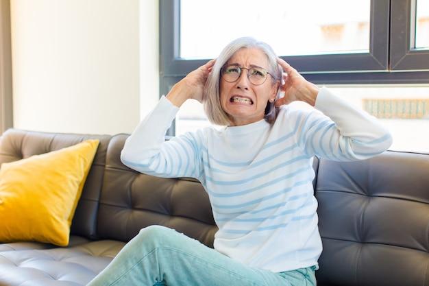 Mulher bonita de meia-idade se sentindo estressada, preocupada, ansiosa ou com medo, com as mãos na cabeça, entrando em pânico com o erro
