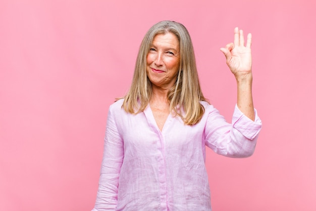 Mulher bonita de meia-idade se sentindo feliz, relaxada e satisfeita, mostrando aprovação com gesto de ok, sorrindo