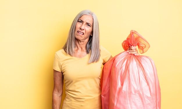 Mulher bonita de meia-idade se sentindo perplexa e confusa. saco plástico garbaje