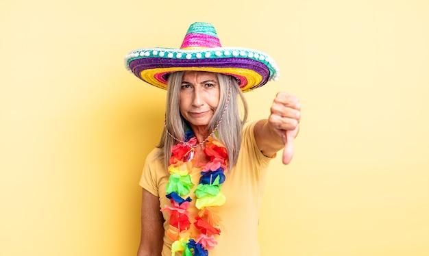 Mulher bonita de meia-idade se sentindo zangada, mostrando os polegares para baixo. conceito de festa mexicana