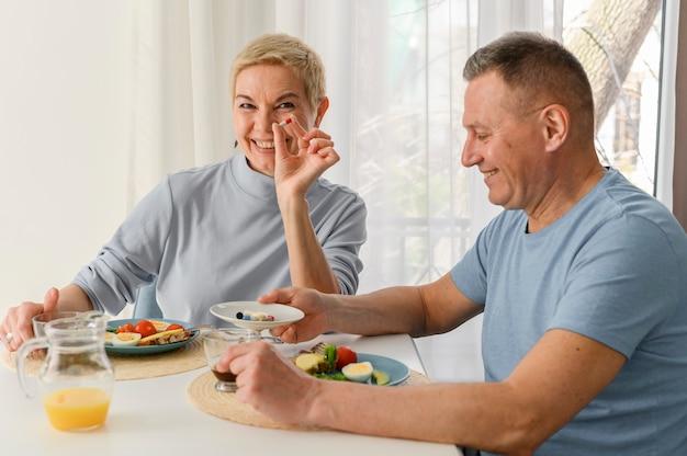 Mulher bonita de meia-idade segurando um remédio sorrindo feliz e positiva tomando suplementos alimentares