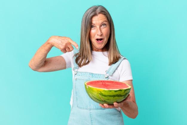 Mulher bonita de meia-idade segurando uma fatia de melancia