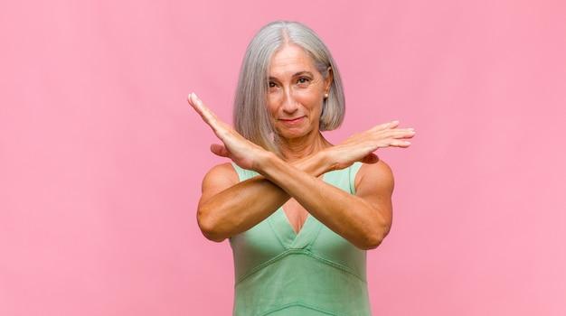 Mulher bonita de meia-idade sorrindo alegre e feliz, apontando para cima com uma mão para copiar o espaço