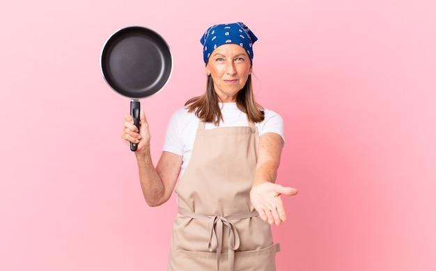 Mulher bonita de meia-idade, sorrindo alegremente com amigável e oferecendo e mostrando um conceito e segurando uma panela. conceito de chef