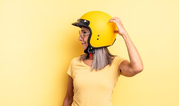 Mulher bonita de meia-idade, sorrindo alegremente e sonhando acordada ou duvidando. conceito de capacete de motocicleta