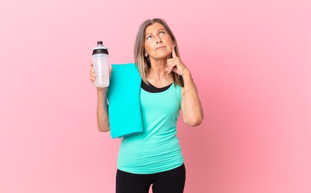 Mulher bonita de meia-idade, sorrindo alegremente e sonhando acordada ou duvidando. conceito de fitness