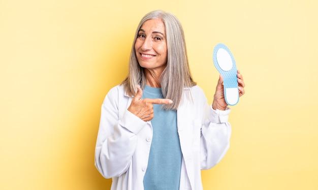 Mulher bonita de meia-idade sorrindo alegremente, sentindo-se feliz e apontando para o lado. conceito de quiropodista