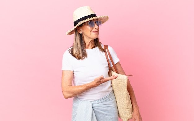 Mulher bonita de meia-idade sorrindo alegremente, sentindo-se feliz e mostrando um conceito. conceito de verão