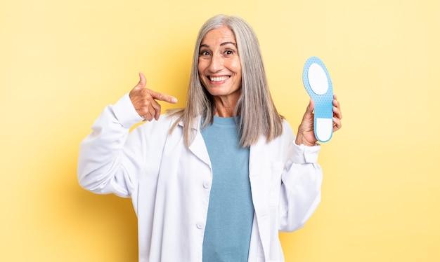 Mulher bonita de meia-idade sorrindo com confiança, apontando para o próprio sorriso largo. conceito de quiropodista