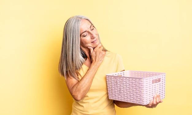 Mulher bonita de meia-idade sorrindo com uma expressão feliz e confiante com a mão no queixo. conceito de cesta vazia