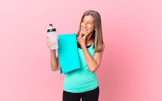 Mulher bonita de meia-idade, sorrindo com uma expressão feliz e confiante com a mão no queixo. conceito de fitness