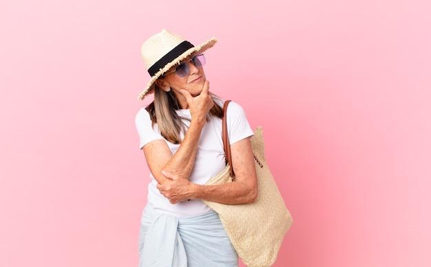 Mulher bonita de meia-idade, sorrindo com uma expressão feliz e confiante com a mão no queixo. conceito de verão
