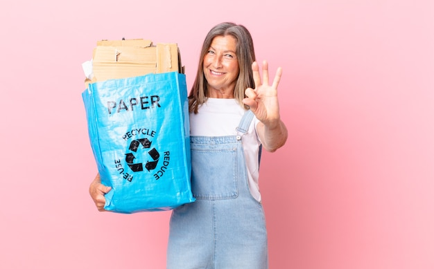 Mulher bonita de meia-idade sorrindo e parecendo amigável, mostrando o conceito número três de reciclagem de papelão