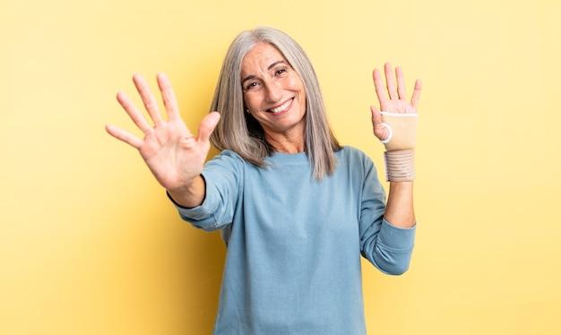 Mulher bonita de meia-idade, sorrindo e parecendo amigável, mostrando o número cinco. conceito de bandagem de mão