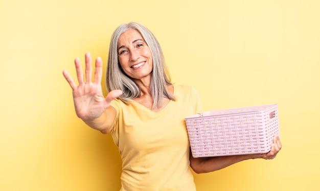 Mulher bonita de meia-idade, sorrindo e parecendo amigável, mostrando o número cinco. conceito de cesta vazia