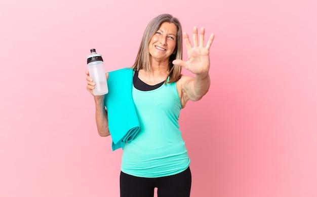 Mulher bonita de meia-idade sorrindo e parecendo amigável, mostrando o número cinco. conceito de fitness