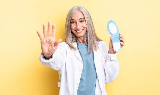 Mulher bonita de meia-idade sorrindo e parecendo amigável, mostrando o número cinco. conceito de quiropodista