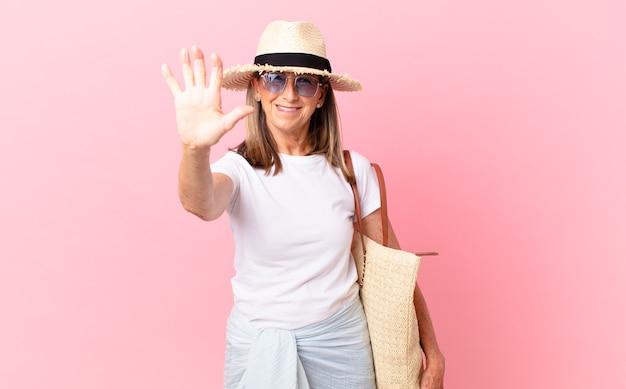 Mulher bonita de meia-idade sorrindo e parecendo amigável, mostrando o número cinco. conceito de verão