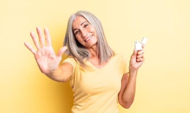 Mulher bonita de meia-idade sorrindo e parecendo amigável, mostrando o número cinco. conceito mais leve