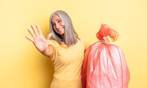 Mulher bonita de meia-idade, sorrindo e parecendo amigável, mostrando o número cinco. saco plástico garbaje