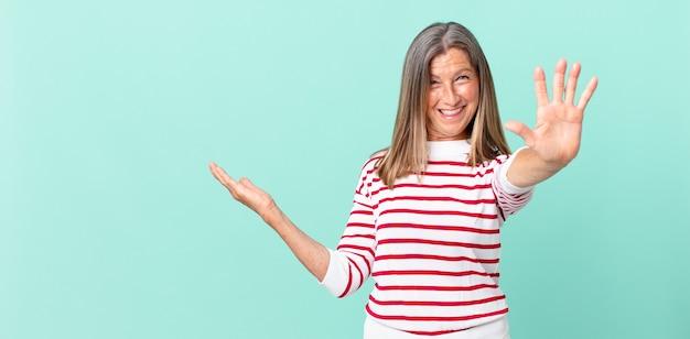 Mulher bonita de meia-idade sorrindo e parecendo amigável, mostrando o número cinco