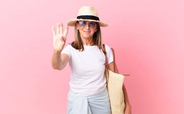 Mulher bonita de meia-idade sorrindo e parecendo amigável, mostrando o número quatro. conceito de verão