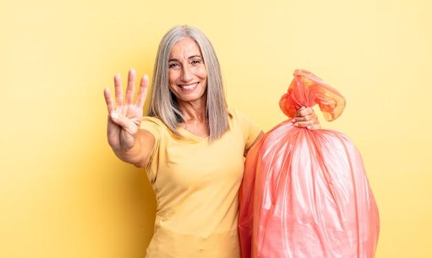 Mulher bonita de meia-idade sorrindo e parecendo amigável, mostrando o número quatro. saco plástico garbaje