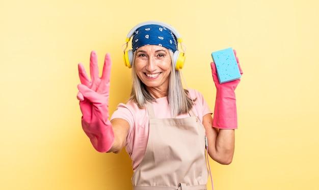 Mulher bonita de meia-idade, sorrindo e parecendo amigável, mostrando o número três. limpador de esfregão