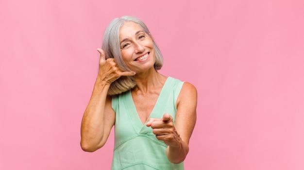 Mulher bonita de meia-idade sorrindo feliz e alegremente, acenando com a mão, dando as boas-vindas e cumprimentando você ou dizendo adeus