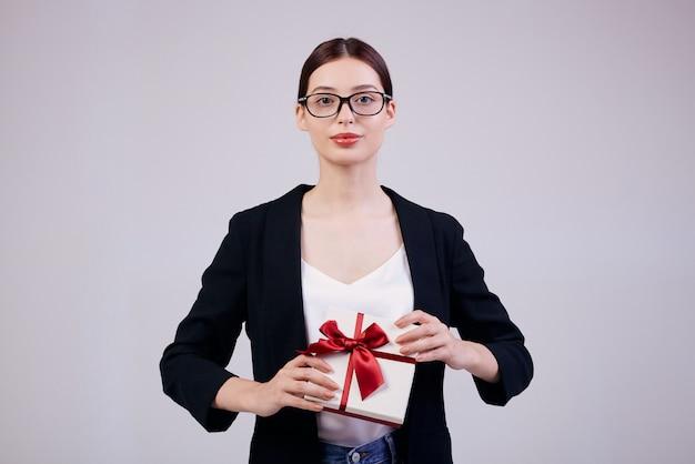 Mulher bonita de negócios de aparência agradável está de pé em cinza com presente nas mãos em uma jaqueta preta e camiseta branca. minuto de felicidade. não precisa trabalhar.