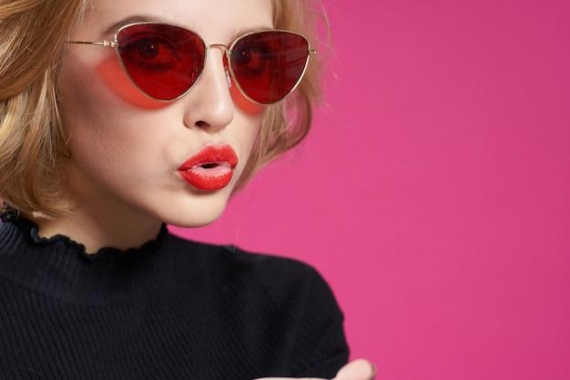 Mulher bonita de óculos escuros brilhante maquiagem jaqueta preta fundo rosa close-up.